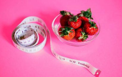 Uma foto de fundo roda, com uma fita metrica e um pote de vidro com morangos