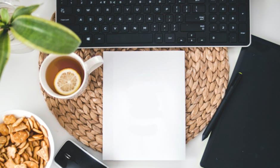 Um notebook sobre a mesa com uma xícara de café, uma folha em branco, celular e caneta para anotações