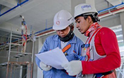 Dois profissionais com equipamentos de segurança em momento de trabalho