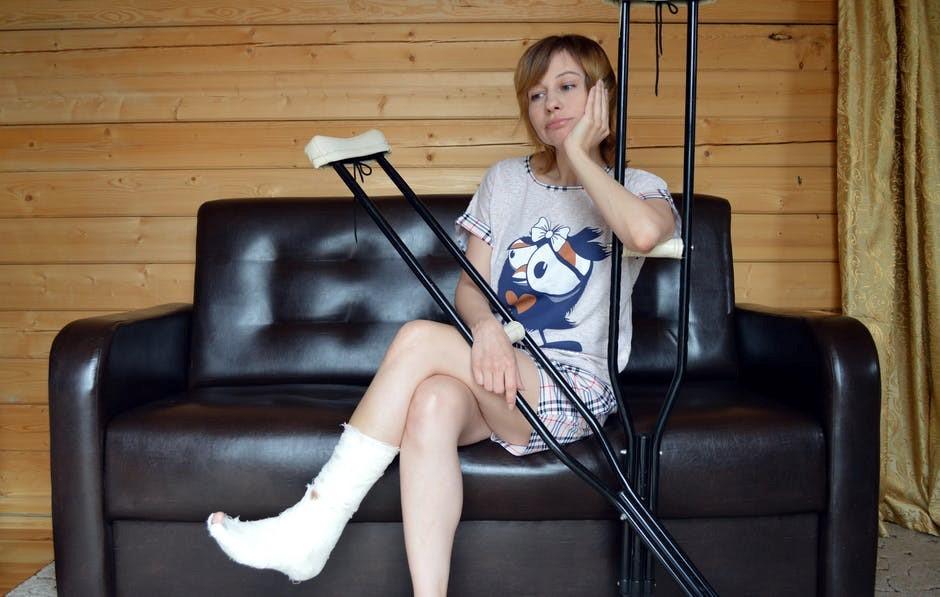 Mulher aborrecida com a perna engessada e uma muleta