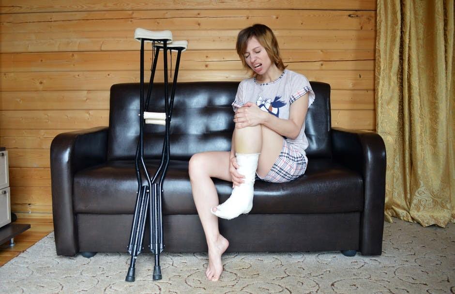 Mulher com cara de paisagem analisando sua perna com gesso