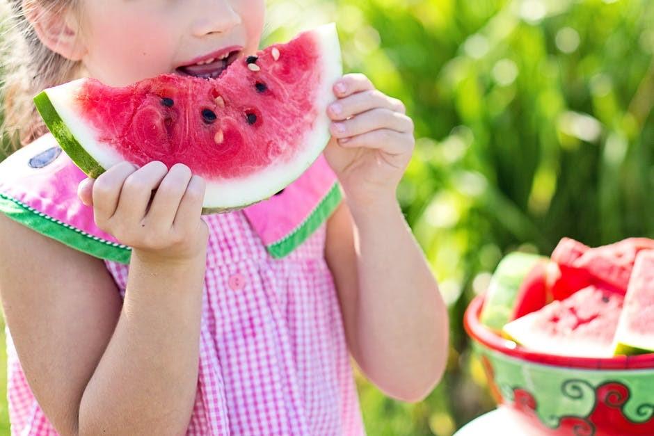 Uma menina comendo melancia